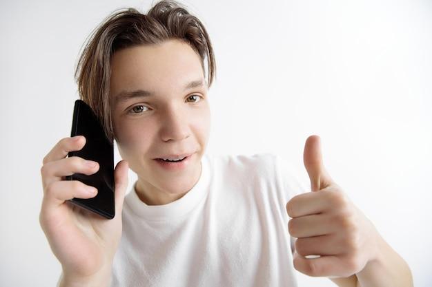 Jonge knappe tiener die het smartphonescherm toont en ok teken ondertekent dat op grijze achtergrond wordt geïsoleerd. menselijke emoties, gezichtsuitdrukking, reclameconcept.
