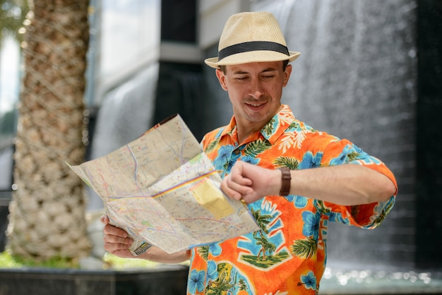 Jonge knappe toeristenmens die kaart leest en de tijd in de stad buiten controleert