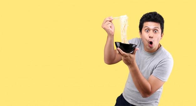 Jonge knappe trendy aziatische man eet lekker warm en pittig instant noedels met stokjes en kom