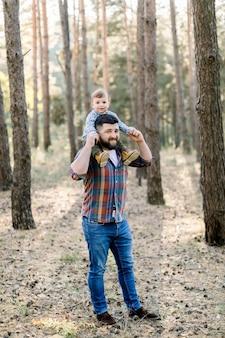 Jonge knappe vader en zoon, stijlvolle vrijetijdskleding dragen, plezier in herfst park
