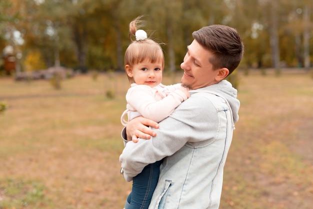 Jonge knappe vader zijn dochtertje in de armen te houden