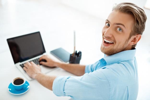 Jonge knappe verraste zekere zakenmanzitting bij lijst die aan laptop met opzij kop van koffie werken. lachend. witte moderne kantoor interieur