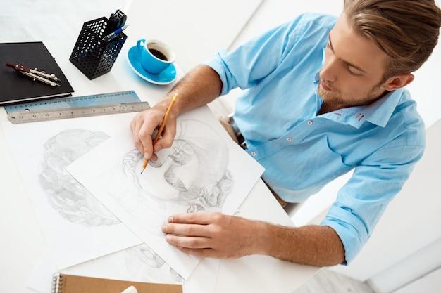 Jonge knappe vertrouwen peinzende zakenman zittend aan tafel met potloodtekening portret witte moderne kantoor interieur muur.