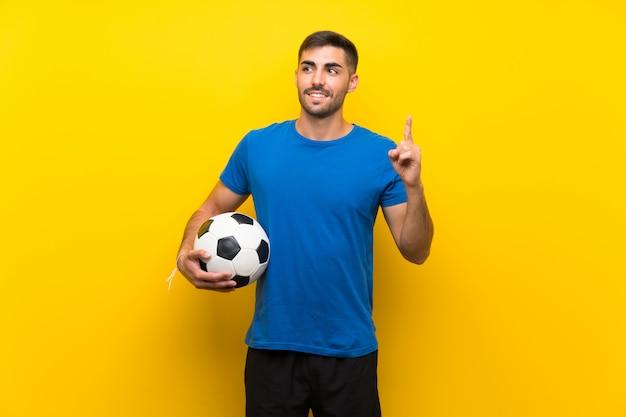 Jonge knappe voetballermens over geïsoleerde gele muur die de oplossing van plan zijn te realiseren terwijl een vinger opheffen