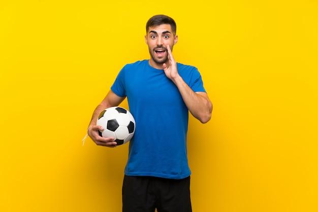 Jonge knappe voetbalstermens over geïsoleerde gele muur met verrassing en geschokte gelaatsuitdrukking