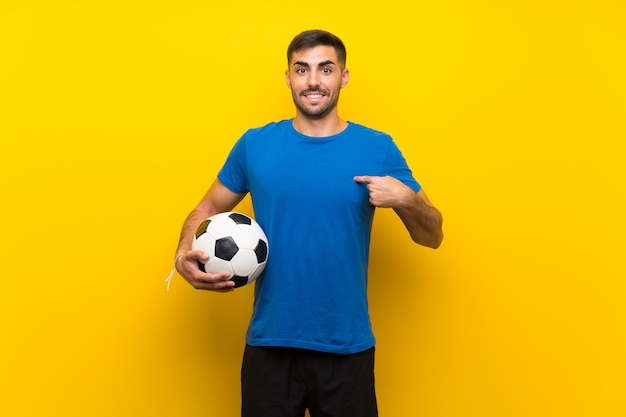 Jonge knappe voetbalstermens over geïsoleerde gele muur met verrassingsgelaatsuitdrukking
