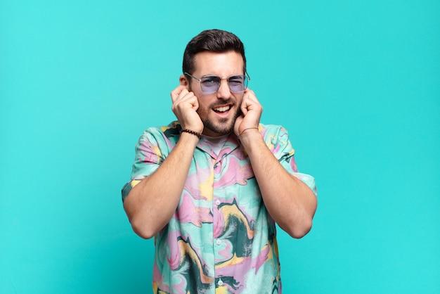 Jonge knappe volwassen man die boos, gestrest en geïrriteerd kijkt en beide oren bedekt met een oorverdovend geluid, geluid of luide muziek. vakantie concept