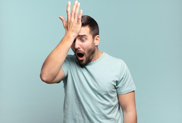 Jonge knappe volwassen man die de handpalm naar het voorhoofd opheft, denkend oeps, na het maken van een domme fout of het herinneren, zich dom voelen