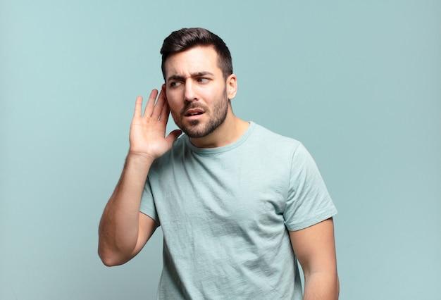 Jonge knappe volwassen man die serieus en nieuwsgierig kijkt, luistert, probeert een geheim gesprek of roddel te horen, afluisteren
