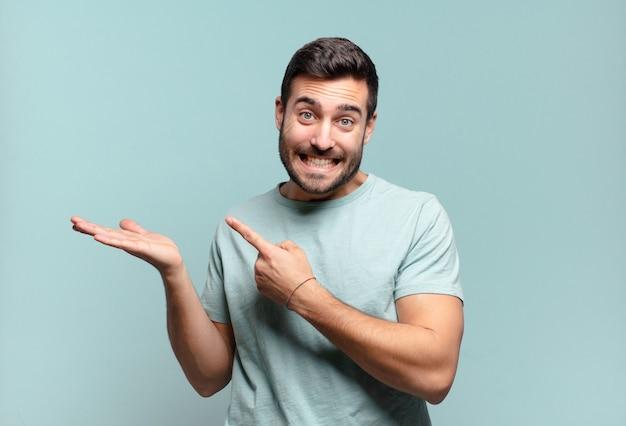 Jonge knappe volwassen man die vrolijk lacht en wijst om de ruimte op de palm aan de zijkant te kopiëren, een object laat zien of er reclame voor maakt