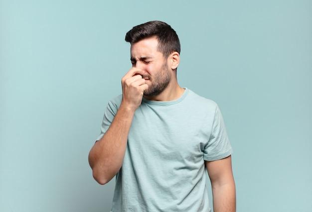 Jonge knappe volwassen man die walgt en neus vasthoudt om te voorkomen dat hij een vieze en onaangename stank ruikt