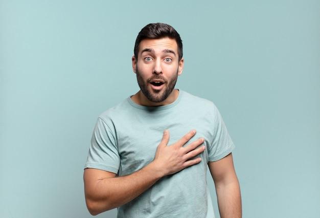 Jonge knappe volwassen man die zich geschokt en verrast voelt, glimlacht, hand ter harte neemt, blij is om degene te zijn of dankbaarheid toont