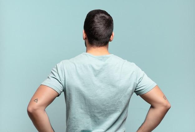 Jonge knappe volwassen man die zich verward of vol voelt of twijfels en vragen, zich afvragend, met de handen op de heupen, achteraanzicht