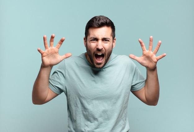 Jonge knappe volwassen man schreeuwend in paniek of woede, geschokt, doodsbang of woedend, met handen naast hoofd
