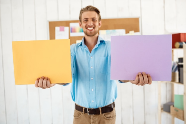 Jonge knappe vrolijke glimlachende zakenman die gekleurde omslagen houdt. witte moderne kantoor interieur.