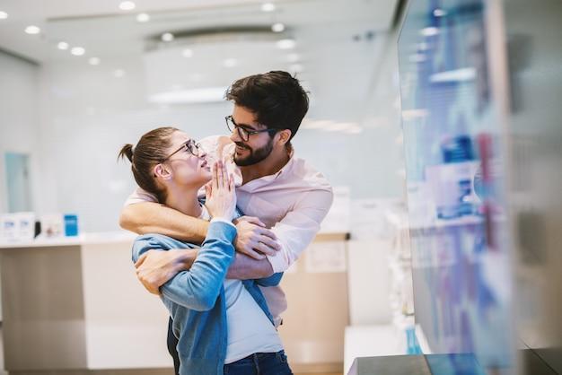 Jonge knappe vrolijke man houdt zijn vriendin van achteren omhelsd terwijl ze hem iets uitlegt.