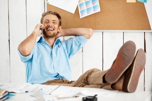 Jonge knappe vrolijke ontspannen lachende vertrouwen zakenman zittend aan tafel met benen praten over telefoon. witte moderne kantoor interieur