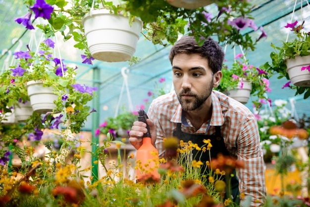 Jonge knappe vrolijke tuinman glimlachen, drenken, bloemen verzorgen
