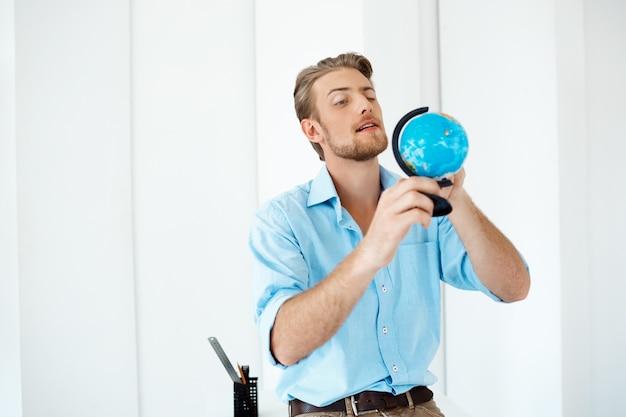 Jonge knappe vrolijke vertrouwen peinzende zakenman permanent aan tafel met kleine wereldbol. witte moderne kantoor interieur