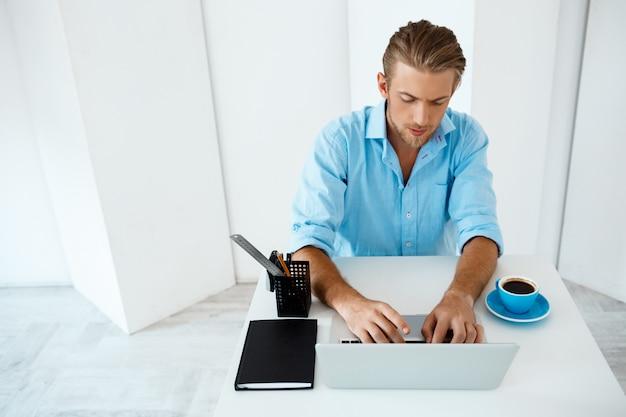 Jonge knappe vrolijke zekere peinzende zakenmanzitting bij lijst die aan laptop met opzij kop van koffie werken. witte moderne kantoor interieur