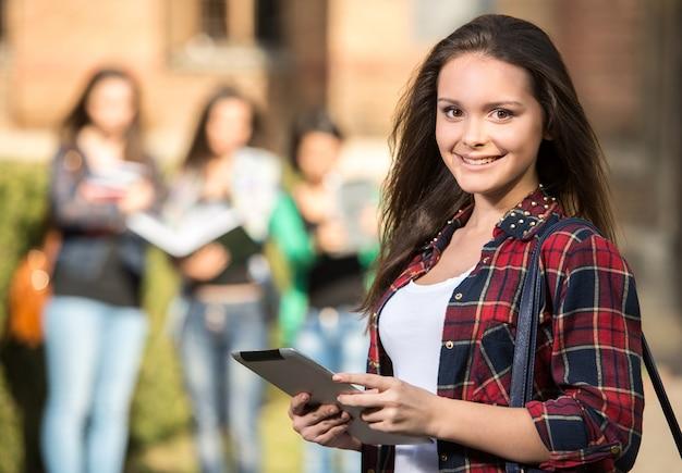 Jonge knappe vrouwelijke student aan de universiteit, buitenshuis.