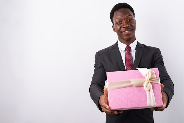 Jonge knappe zakenman bedrijf geschenkdoos tegen wit