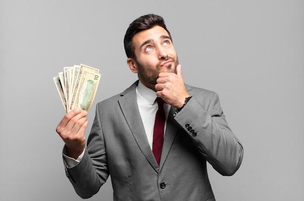 Jonge knappe zakenman denkt, voelt zich twijfelachtig en verward, met verschillende opties, zich afvragend welke beslissing hij moet nemen. rekeningen of geld concept
