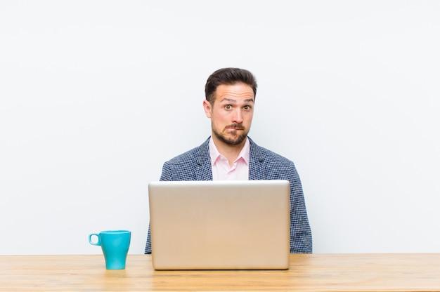 Jonge knappe zakenman die clueless, verward en onzeker voelen over welke te kiezen optie, die het probleem proberen op te lossen