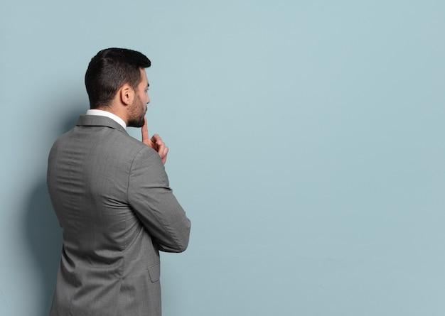 Jonge knappe zakenman die denkt of twijfelt. opties vergelijken