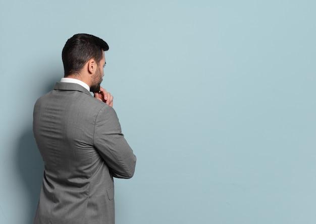 Jonge knappe zakenman die denkt of twijfelt