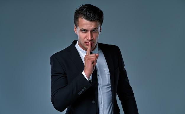 Jonge knappe zakenman die een elegant pak draagt dat over een geïsoleerde grijze achtergrond staat en vraagt om stil te zijn met de vinger op de lippen. stilte en geheim concept.