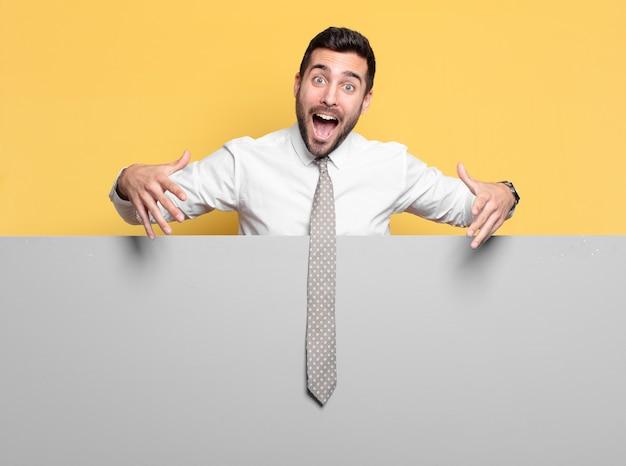Jonge knappe zakenman die een lege plek naar je concept wijst of toont