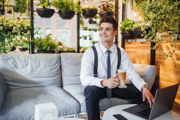Jonge knappe zakenman die een wit overhemd en stropdas draagt, werkende laptop