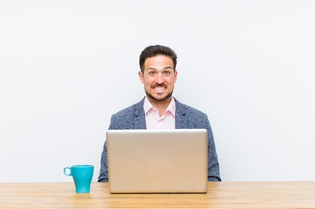 Jonge knappe zakenman die gelukkig en mal met een brede pret gekke glimlach en wijd open ogen kijkt