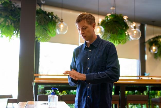 Jonge knappe zakenman die handdesinfecterend middel gebruikt als juiste hygiënetiquette bij de koffiewinkel