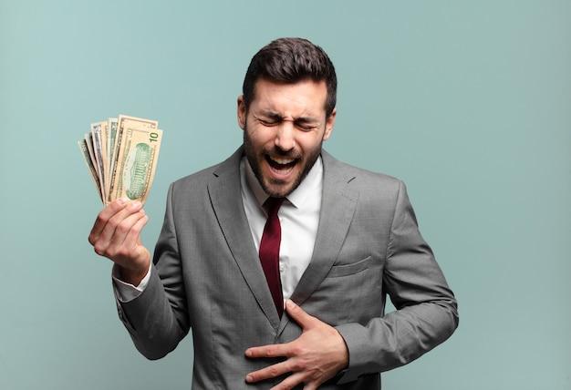 Jonge knappe zakenman die hardop lacht om een of andere hilarische grap, zich gelukkig en opgewekt voelt, plezier heeft. rekeningen of geld concept