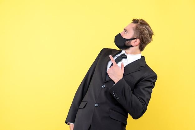 Jonge knappe zakenman die met vinger vooruit iets met verbaasde uitdrukking op geel richt