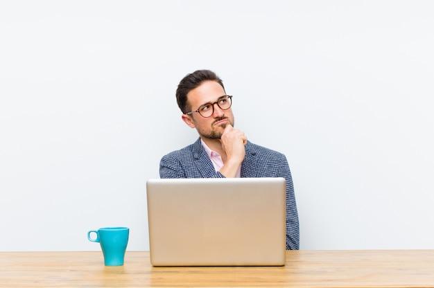 Jonge knappe zakenman die nadenkend voelen, ideeën benieuwd zijn of verbeelden, dagdromen en omhoog kijken om ruimte te kopiëren