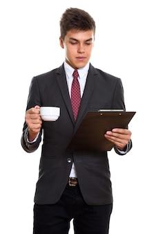 Jonge knappe zakenman die op klembord leest terwijl hij koffiekop houdt