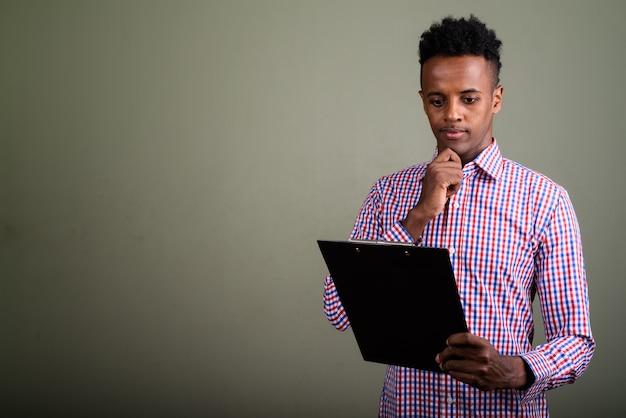 Jonge knappe zakenman die paars geruit overhemd draagt