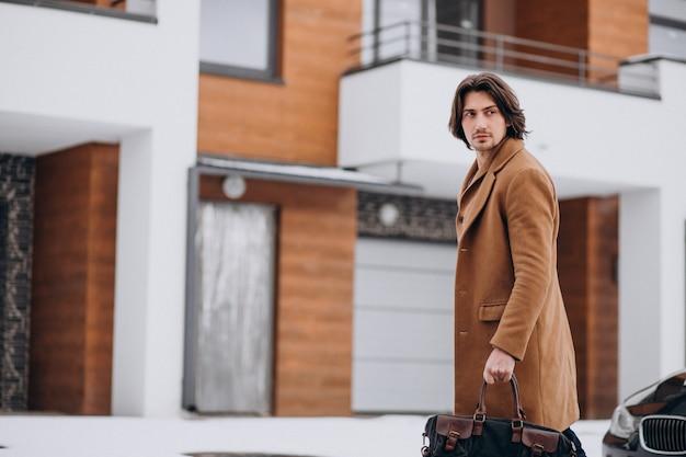Jonge knappe zakenman die van het huis naar zijn auto loopt