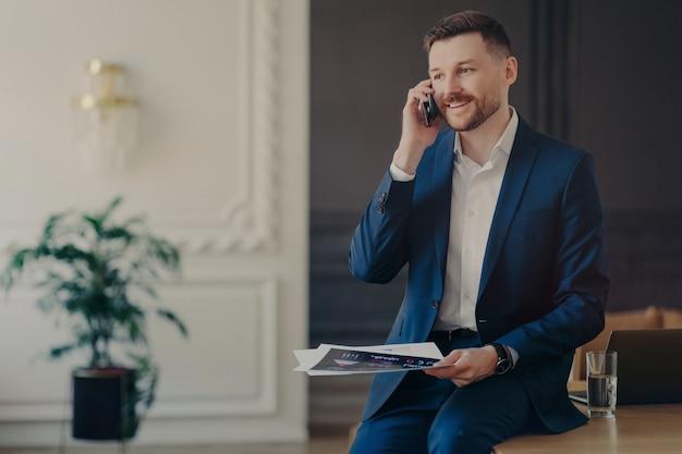 Jonge knappe zakenman die vanuit huis werkt, mannelijke ondernemer in formeel pak praten aan de telefoon op kantoor, glimlachend zakelijke ideeën bespreken met copartner, laptop en glas water op bureau hebben