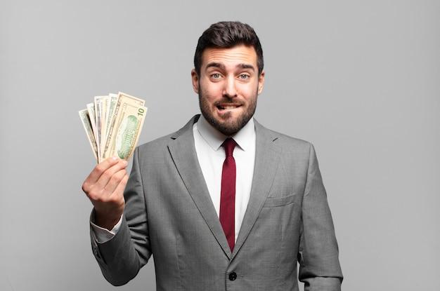 Jonge knappe zakenman die verbaasd en verward kijkt, lip bijt met een nerveus gebaar, niet wetend het antwoord op het probleem. rekeningen of geld concept