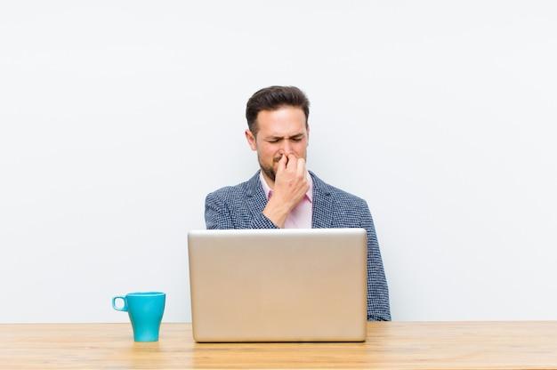 Jonge knappe zakenman die walgt, neus vasthouden om te voorkomen dat hij een vuile en onaangename stank ruikt