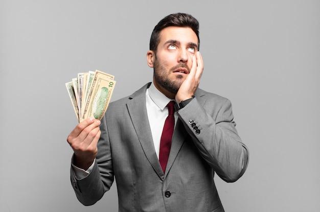 Jonge knappe zakenman die zich verveeld, gefrustreerd en slaperig voelt na een vermoeiende, saaie en vervelende taak, gezicht met de hand vasthoudend. rekeningen of geld concept