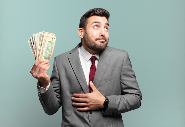 Jonge knappe zakenman die zijn schouders ophaalt, zich verward en onzeker voelt, twijfelt met gekruiste armen en een verbaasde blik. rekeningen of geld concept