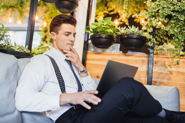 Jonge knappe zakenman draagt een wit overhemd en stropdas, werkende laptop in een stijlvol modern kantoor.