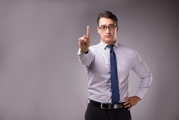 Jonge knappe zakenman dringende knopen op grijs