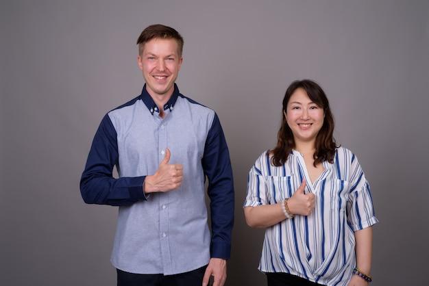 Jonge knappe zakenman en volwassen aziatische zakenvrouw