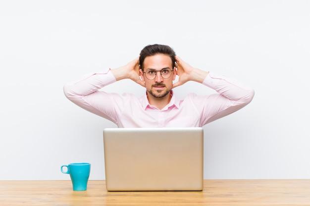 Jonge knappe zakenman gevoel gestrest, bezorgd, angstig of bang, met handen op het hoofd, in paniek bij vergissing